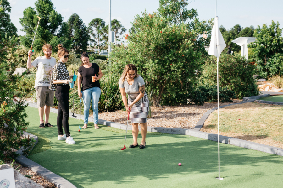 group of people playing mini golf